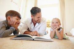 Vader die met twee jonge geitjes een verhaalboek lezen Stock Fotografie