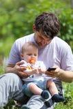 Vader die mobiel met een baby op zijn overlapping gebruiken Stock Afbeelding