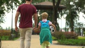 Vader die naar huis met zoon na school lopen, die sportklassen, voetbal bespreken stock video