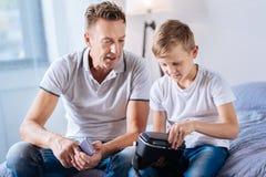 Vader die op zijn zoon letten proberend om VR-hoofdtelefoon te openen Stock Afbeelding