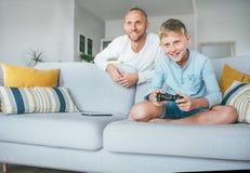 Vader die op zijn zoon letten speel TV-videospelletje die gamepad gebruiken stock afbeeldingen
