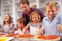 Vader die pizza met zijn jonge geitjes maken Stock Afbeeldingen