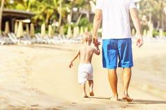 Vader die pret op het strand met zijn kleine zoon hebben stock foto