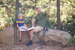 Vader die richting tonen aan zoon in bos royalty-vrije stock fotografie