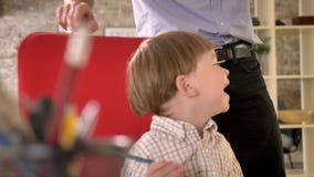 Vader die rond zijn kleine zoon op stoel, gelukkig jong geitje omcirkelen die en in modern bureau toejuichen zitten stock footage