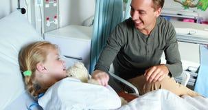 Vader die teddybeer geven aan haar zieke dochter stock videobeelden