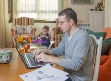 Vader die in van de huisbureau en zoon het spelen werken Stock Foto's
