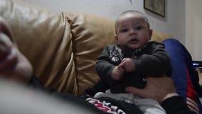 Vader die vier maanden oud houden baby die spreekt en grappige gezichten maakt stock footage