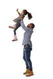 Vader die weinig dochter in de lucht werpt Royalty-vrije Stock Afbeeldingen