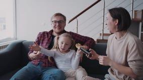 Vader die weinig dochter koesteren terwijl zijn vrouw cellulair gebruiken stock footage