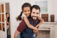 Vader die weinig dochter vervoeren per kangoeroewagen en bij camera thuis glimlachen Royalty-vrije Stock Afbeeldingen