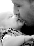 Vader die zijn baby kust Stock Afbeelding