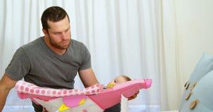 Vader die zijn baby in slaapkamer 4k kijken stock footage