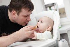 Vader die zijn baby voedt Stock Afbeeldingen