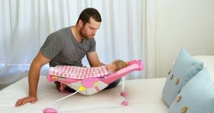 Vader die zijn baby zetten aan slaap op babybed 4k stock footage
