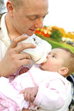 Vader die zijn babymeisje met een fles melk voedt Stock Afbeelding