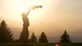 Vader die zijn dochter in het park opheffen terwijl zonsondergang stock footage