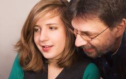 Vader die zijn dochter met thuiswerk helpt Stock Foto's