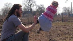 Vader die zijn dochter op de schommeling duwen terwijl het hebben van pret in het park stock footage