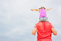 Vader die zijn dochter op schouders vervoeren Stock Afbeeldingen