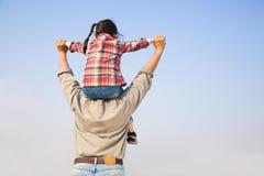 Vader die zijn dochter op schouders vervoert Stock Afbeeldingen