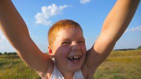 Vader die zijn gelukkige zoon in een weide op een zonnige dag spinnen De papa roteert rond glimlachende jongen bij aard Sluit omh stock footage