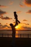 Vader die zijn jong geitje omhoog in de lucht op het strand, silhouet s werpen Royalty-vrije Stock Afbeelding
