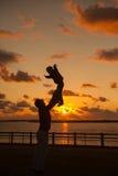 Vader die zijn jong geitje omhoog in de lucht op het strand, silhouet s werpen Royalty-vrije Stock Foto's