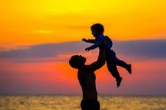 Vader die zijn jong geitje omhoog in de lucht op het strand, silhouetschot werpen Stock Foto