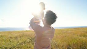 Vader die zijn jong geitje omhoog in de lucht op het strand werpt stock footage