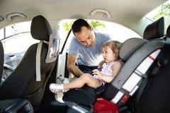 Vader die zijn kinddochter zetten in haar autozetel in de auto stock foto