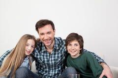 Vader die zijn kinderen koesteren Stock Foto