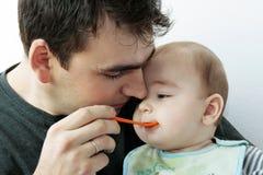 Vader die zijn kleine baby voedt Stock Foto's