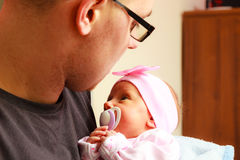 Vader die zijn pasgeboren baby gevoelig houden Stock Foto's