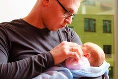 Vader die zijn pasgeboren baby gevoelig houden Stock Foto
