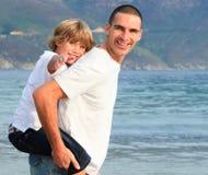 Vader die zijn rit van het zoonsvervoer per kangoeroewagen op het strand geeft Royalty-vrije Stock Fotografie