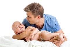 Vader die zijn schreeuwende baby proberen te troosten Stock Foto