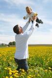 Vader die zijn zoon in de hemel opheft royalty-vrije stock foto