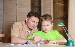 Vader die zijn zoon met modelvliegtuig helpen De mens en de jongen maken vliegtuigenmodel Royalty-vrije Stock Fotografie