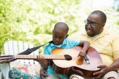 Vader die zijn zijn zoon teaaching om de gitaar te spelen Stock Fotografie