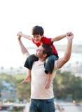 Vader die zijn zoonsvervoer per kangoeroewagen geeft Royalty-vrije Stock Fotografie