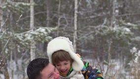 Vader die zoon in lucht, langzame motie werpen Vader en zoon die pret in een de winterpark hebben, vader die jonge jongen werpen  stock videobeelden