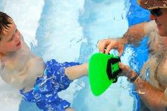 Vader die zoon in pool helpt Stock Afbeeldingen