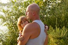 Vader dragende dochter in zijn handen die haar beschermen stock fotografie