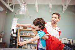 Vader dragende zoon die superherokostuum dragen Stock Foto's