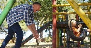 Vader duwende zoon in schommeling bij speelplaats 4k stock video