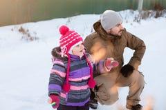Vader en baby die, de winter, sneeuw samen lopen Stock Fotografie
