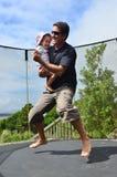 Vader en baby die op trampoline springen Royalty-vrije Stock Afbeeldingen