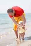 Vader en baby op strand Royalty-vrije Stock Afbeeldingen