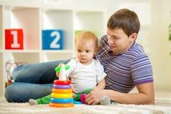 Vader en babyjongensspel samen binnen thuis Royalty-vrije Stock Afbeeldingen